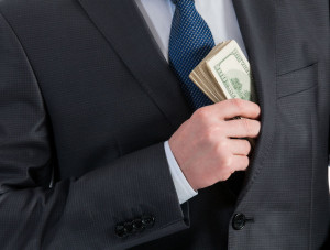 49258230 - businessman putting money in his pocket - closeup shot