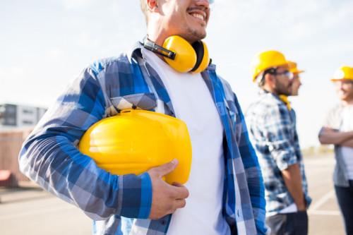 close up of builder holding hardhat at building